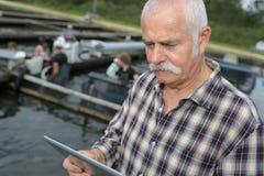 Skaldjur- eller fisklantgårdchef som beställer tillförsel på minnestavlan royaltyfria bilder