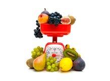 Skalen der frischen Frucht und der Küche auf einem weißen Hintergrund Stockbilder