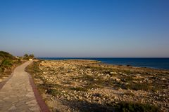 Skalista ścieżka wzdłuż Śródziemnomorskiego wybrzeża w Cypr Piękny widok skalisty wybrzeże i błękitny morze zdjęcia royalty free
