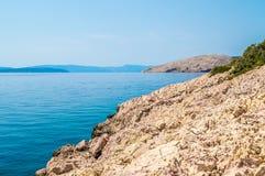 Skalista linia brzegowa z kryształem - jasny błękitny Adriatycki morze z wyspą Fotografia Stock