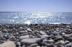 Skalista plaża na słonecznym dniu oceanem Zdjęcie Stock