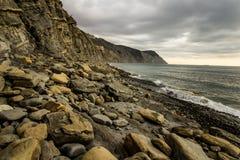Skalista plaża przy zmierzchem z zadziwiającym światłem Obrazy Stock