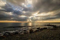 Skalista plaża przy zmierzchem z zadziwiającym światłem obraz stock
