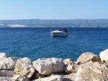 Skalista plaża w Chorwacja z łodzią w tle obraz royalty free