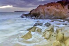Skalista plaża podczas zmierzchu Obraz Stock