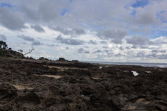Skalista plaża z chmurnym niebem fotografia stock
