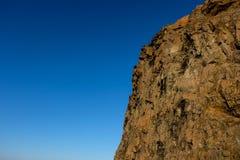 Skalistej góry strona z jaskrawym niebieskim niebem w tle Zdjęcia Royalty Free