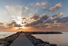 Skalisty jetty, molo przy wschód słońca z/dramatycznego chmurnego nieba i gładkiego morza boną, Cala, Mallorca, Spain fotografia royalty free