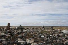 Skalisty krajobraz posypujący z malutkim Inuksuit wzdłuż Kanada ` s arktycznego wybrzeża Obraz Royalty Free