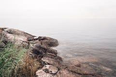 Skalisty wybrzeże i gładzi wodę zdjęcia royalty free