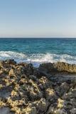 Skalisty wybrzeże, turkusowy morze z foamy wodą, bezchmurny niebo obrazy stock