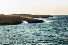 Skalisty wybrzeże, turkusowy morze z foamy wodą, bezchmurny niebo zdjęcia royalty free