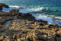 Skalisty wybrzeże, turkusowy morze z foamy wodą, bezchmurny niebo zdjęcie royalty free