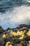Skalisty wybrzeże, turkusowy morze z foamy wodą, bezchmurny niebo zdjęcia stock