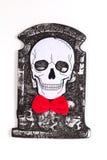 Skalle med det röda bandet på kyrkogården Royaltyfri Fotografi