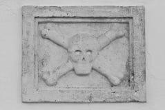 Skalle- och Crossbonesstenskulptur arkivfoton