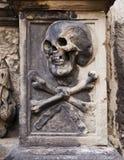 Skalle och korslagda benknotor på gravstenen Royaltyfri Bild