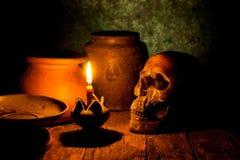 Skalle och stearinljus med ljusstaken på trä Arkivfoto