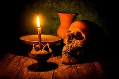 Skalle och stearinljus med ljusstaken på trä Royaltyfri Bild