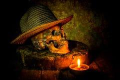 Skalle och stearinljus med ljusstaken på trä Royaltyfria Bilder