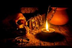 Skalle och stearinljus med ljusstaken på trä Royaltyfri Foto
