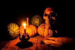 Skalle och stearinljus med ljusstaken på trä Arkivbild