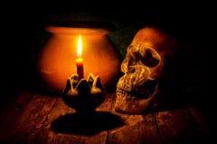 Skalle och stearinljus med ljusstaken på träbakgrund, fortfarande li Arkivfoto