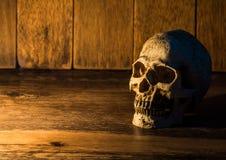 Skallen förläggas på en trätabell Bakgrunden är en träplatta och ljus från stearinljuset till skallen Royaltyfri Fotografi