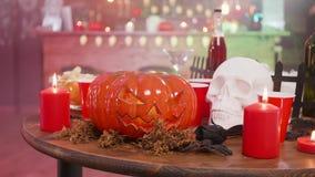 Skallen och stålar-nolla-lyktan på en trätabell i en halloween dekorerade baren stock video