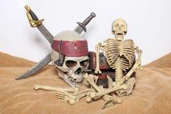 Skallen och svärd piratkopierar av det karibiskt med den gamla träbröstkorgen på det bruna tyget Arkivbilder