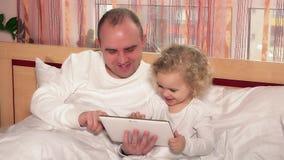 Skallig fader med den lilla gulliga leken för dotterflickalek på minnestavladatoren i säng stock video