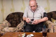 Skallig gamal man som kontrollerar mediciner med BP apparaturen Fotografering för Bildbyråer