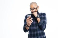 Skallig man för gladlynt afrikansk amerikan som använder smartphonen och att skratta arkivbild