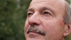Skallig man för pensionär med mustaschen som fast ser upp arkivfilmer