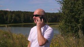 Skallig man i solglasögon som kallar till mobiltelefonen i grön skog med sjön lager videofilmer