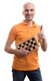 Skallig man som rymmer ett schackbräde Arkivbild