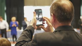 Skallig man som skjuter en smartphoneutmärkelse på turneringen Arkivfoto