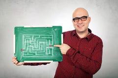 Man med labyrinten på den svart tavlan Royaltyfri Foto
