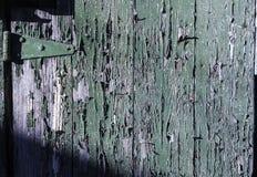 Skalning av grön målarfärg på det gamla trä och gångjärnet arkivbilder
