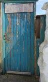 Skalning av målarfärg på den blåa dörren Brixham Torbay Devon Endland UK Arkivfoto