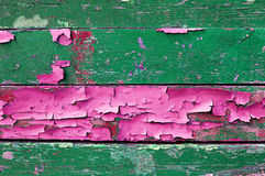 Skalning av målarfärg på gammalt ridit ut trä med skalningsmålarfärg av gröna och rosa färger texturerade träbakgrund Royaltyfri Bild