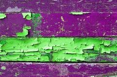 Skalning av målarfärg på gammalt ridit ut trä med skalningsmålarfärg av gröna och violetta färger texturerade träbakgrund Royaltyfria Foton