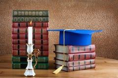 Skalowania mortarboard na górze sterty książki na drewnianym stole obraz royalty free