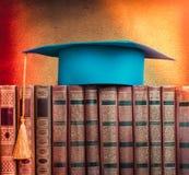 Skalowania mortarboard na górze sterty książki na abstrakta plecy Obraz Royalty Free
