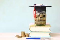 Skalowanie kapelusz na szklanej butelce książkach na białym tle i, Ratuje pieniądze dla edukacji pojęcia zdjęcia royalty free