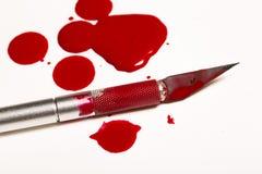Skalpellblad med blod Arkivbild