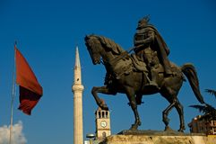 Skanderbeg, Tirana, Albania. The equestrial statue of the great Albanian hero of Skanderbeg with a minaret and the Albanian national flag Royalty Free Stock Images