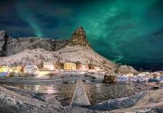 Skandinavisch dorp met aurora borealis over sneeuwberg stock foto