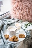 Skandinavisch stijlontbijt, kop van koffie en koekjes op comfortabele vensterbank met warm deken en hoofdkussen royalty-vrije stock fotografie