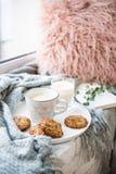 Skandinavisch stijlontbijt, kop van koffie en koekjes op comfortabele vensterbank met warm deken en hoofdkussen royalty-vrije stock foto's